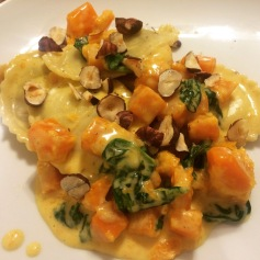 Mushroom ravioli with roasted butternut squash, hazelnuts and spinach in a cream sauce