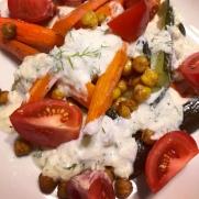 Vegan tzatziki sauce smothering a fresh vegetable and garbanzo bean salad